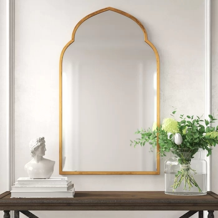 The mirror hanging above a brown desk
