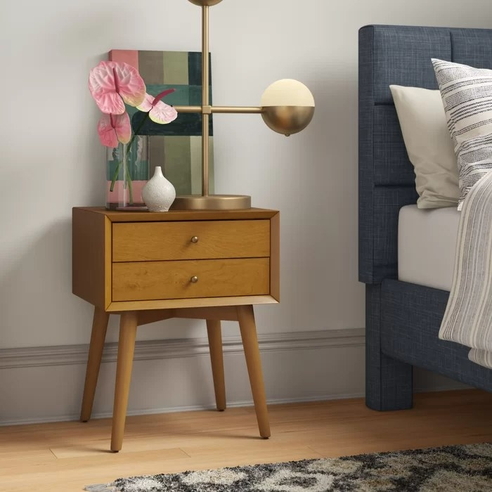 The nightstand with lamp and decorative items on top