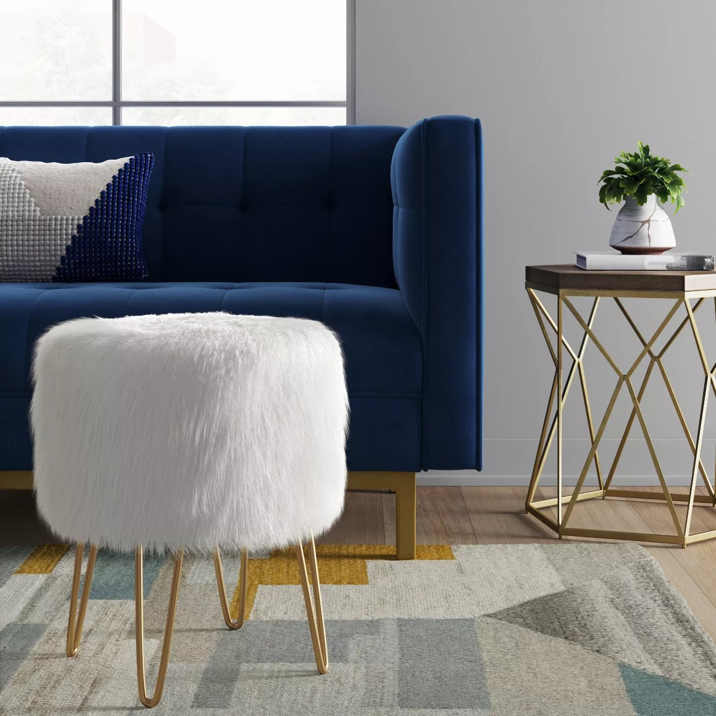 The white faux fur ottoman with metal pin legs