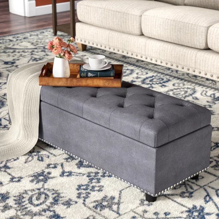The grey ottoman, closed, with serving tray and blanket on top