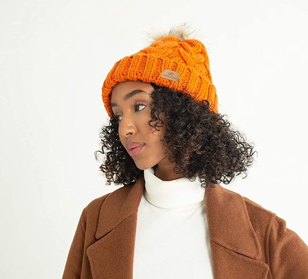 Model in the orange hat with a faux fur pompom