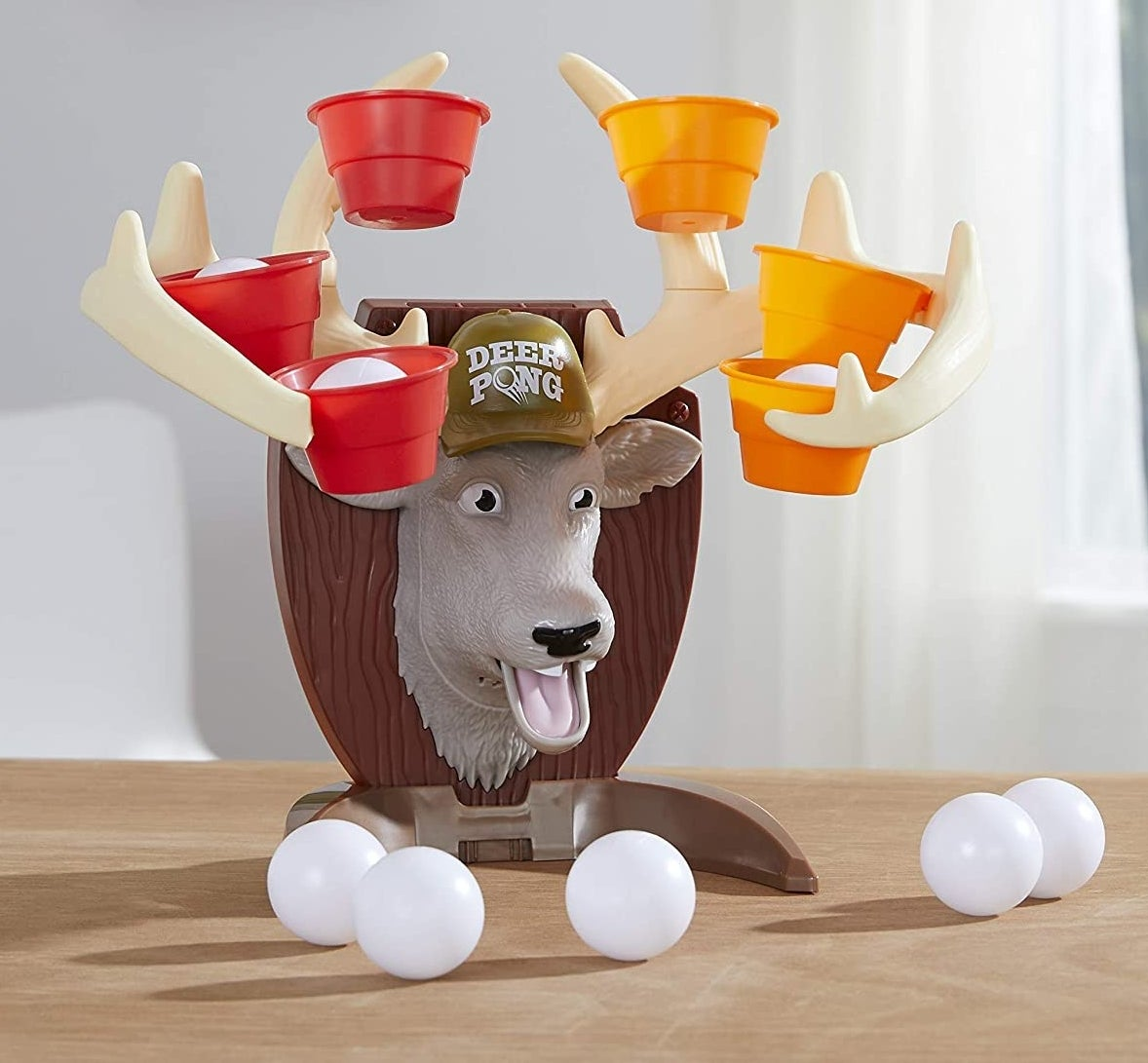A plastic deer head with colorful cups on the antlers and white ping pong balls