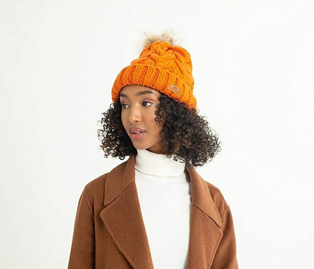 Model in the orange hat with faux fur pompom