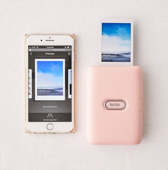 Fujifilm mini link smartphone printer in pink next to an iPhone