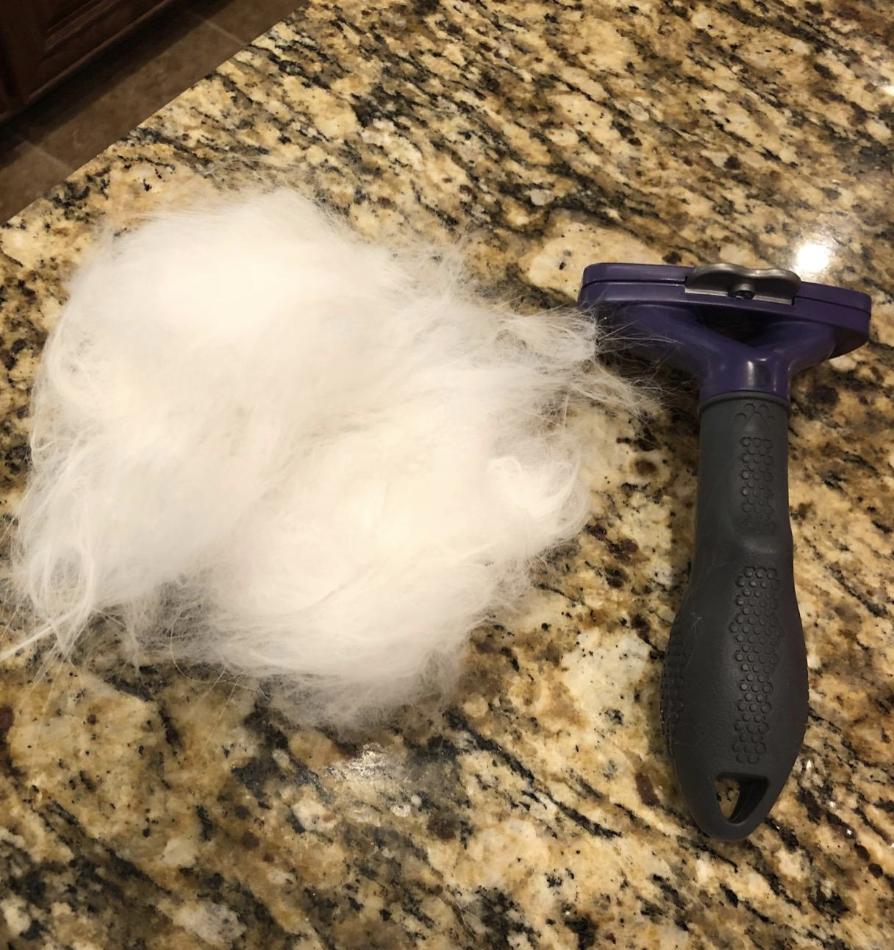 The furminator tool next to a pile of cat hair