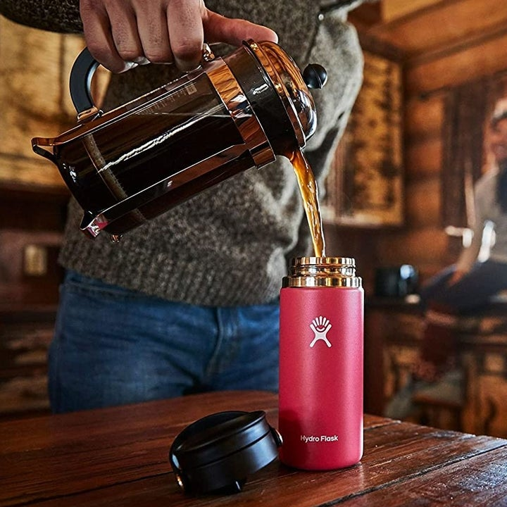 model pouring coffee from a french press into a red travel mug