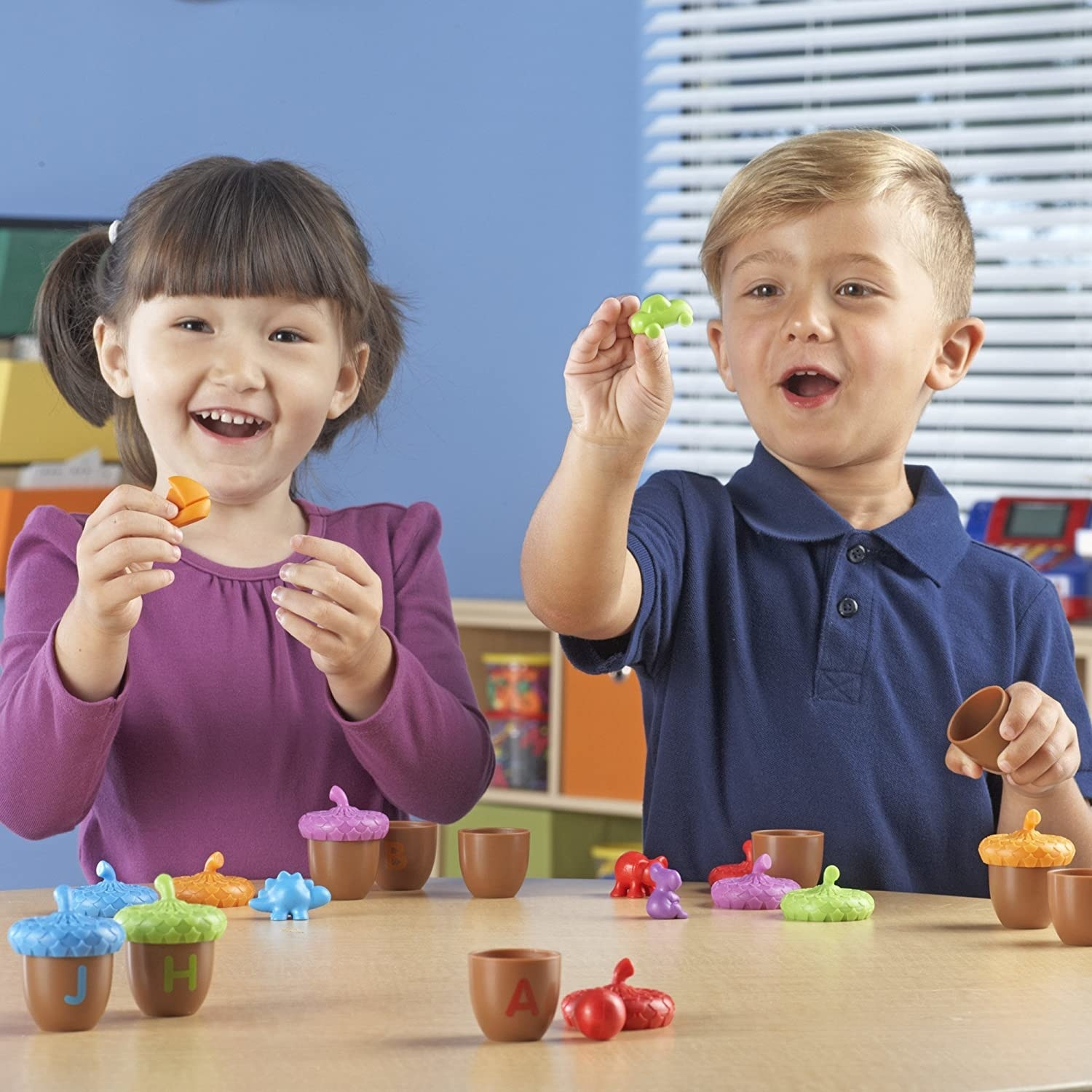 Two child models play with brown plastic acorn toys with colorful tops