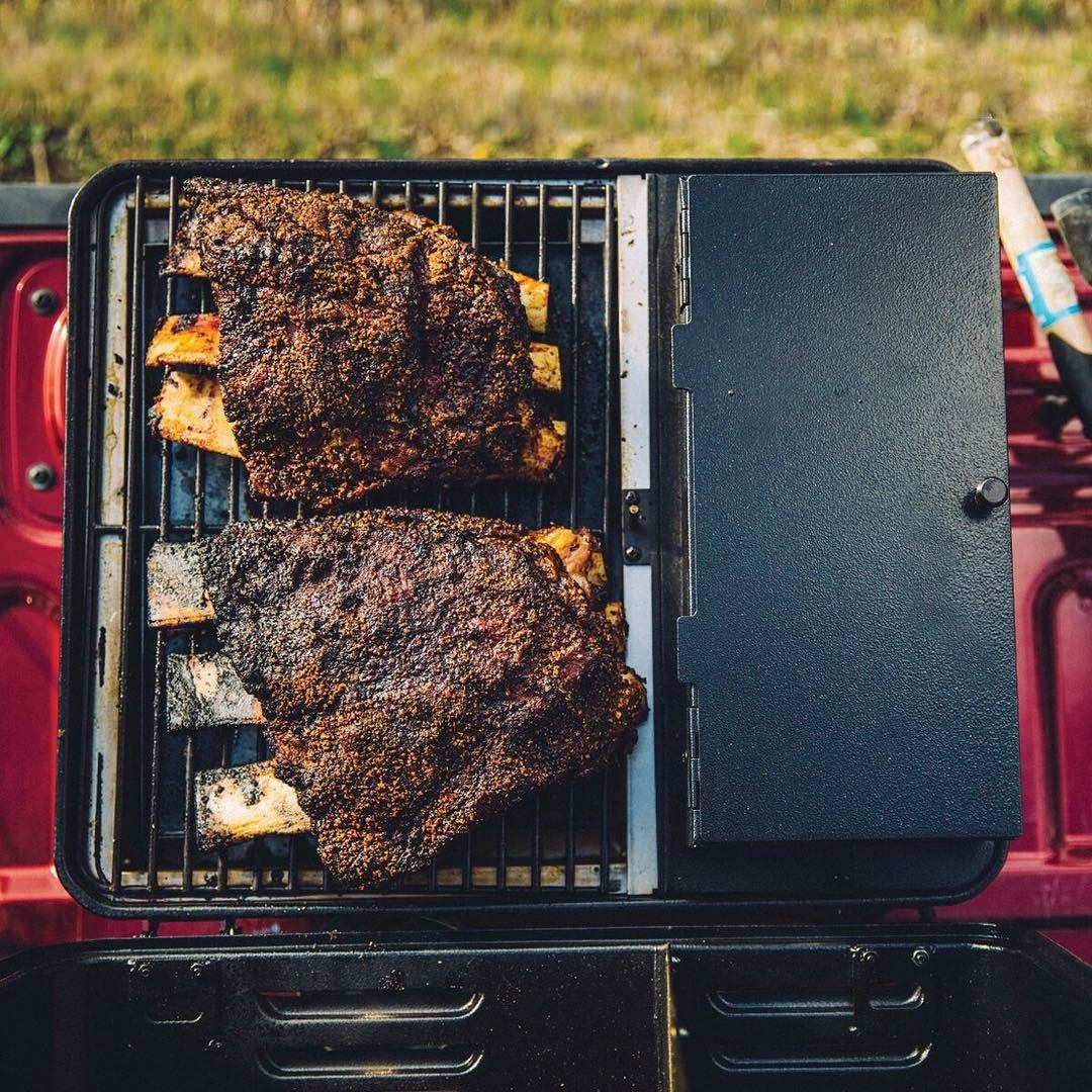The portable grill set up on truck bed with large ribs cooking