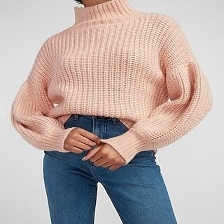 Model wearing light pink balloon-sleeve sweater with jeans