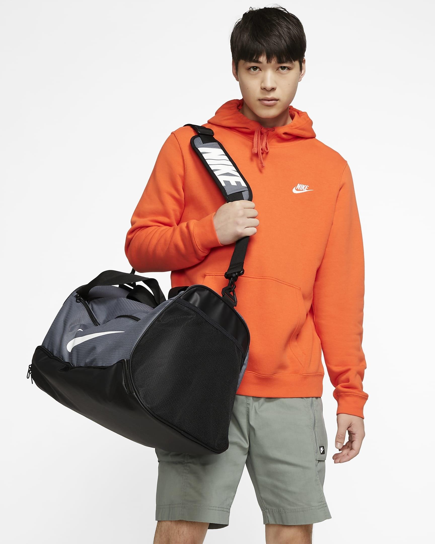 Model carrying black and grey duffle bag