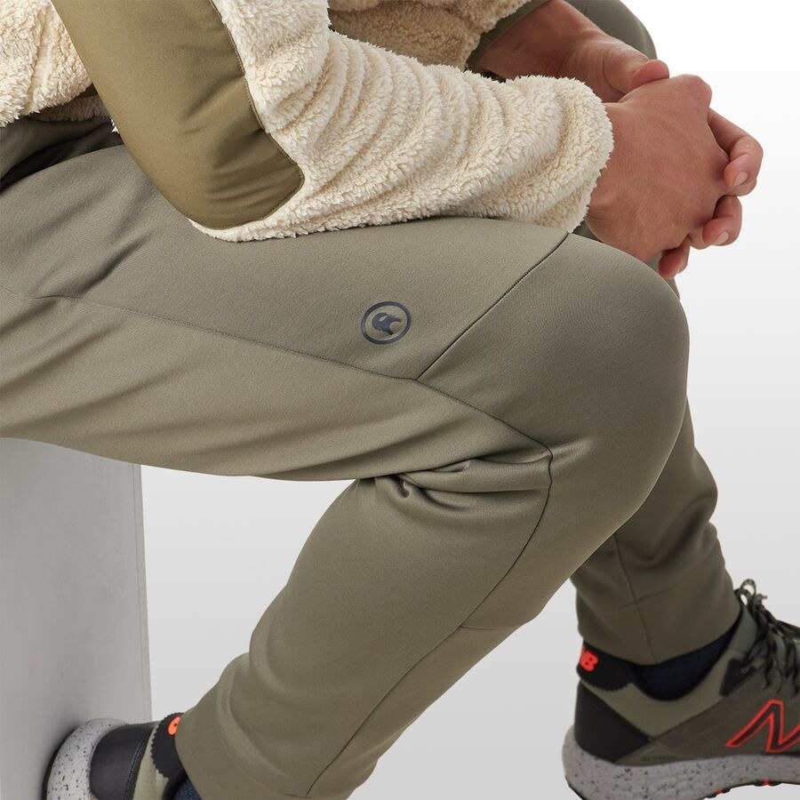 a model wearing the pants in olive color and sitting down