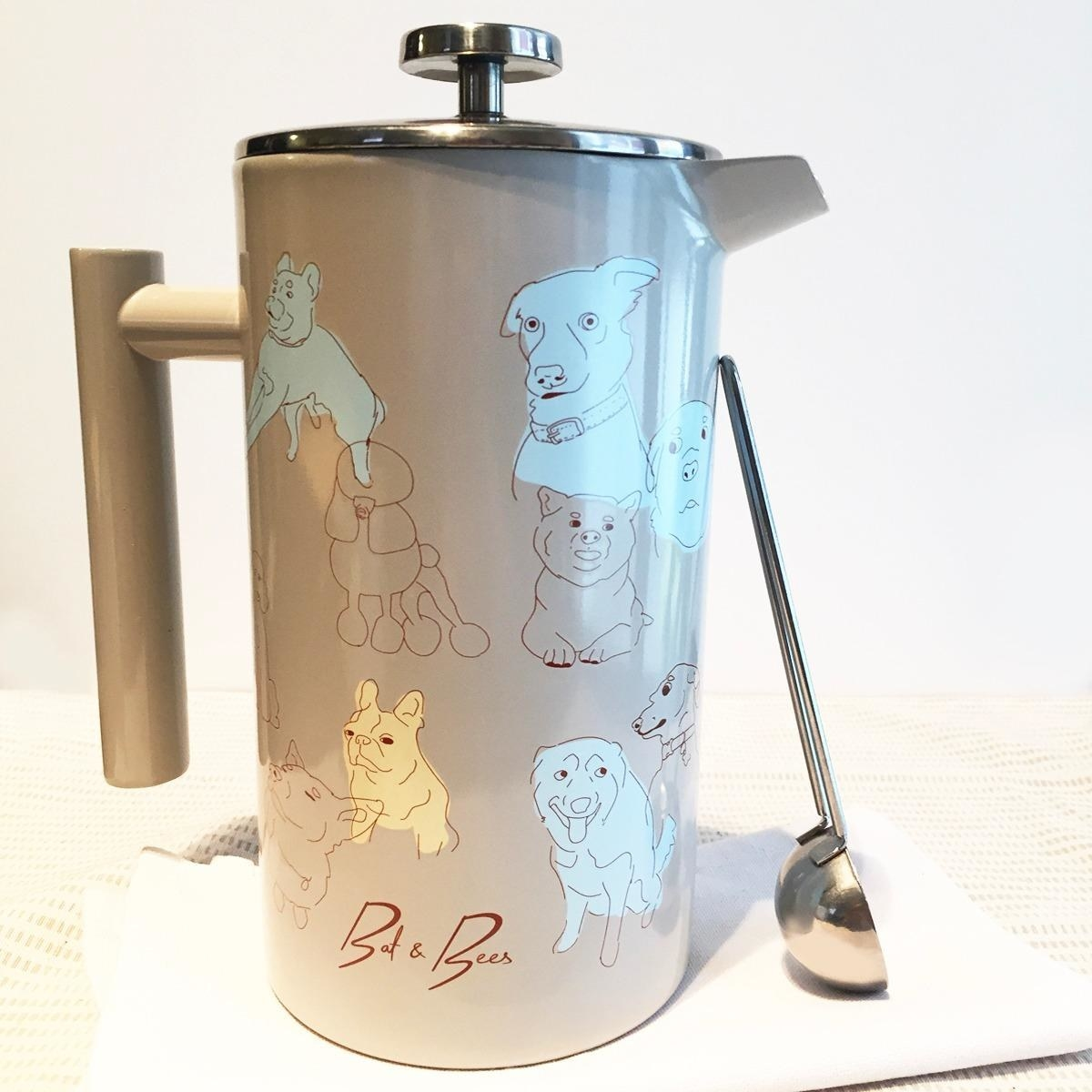 tan opaque french press with blue and yellow drawings of dogs