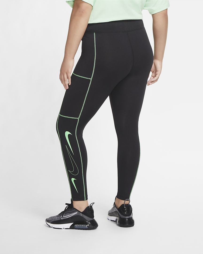 Model wearing black leggings with bright green Nike swoosh and design details