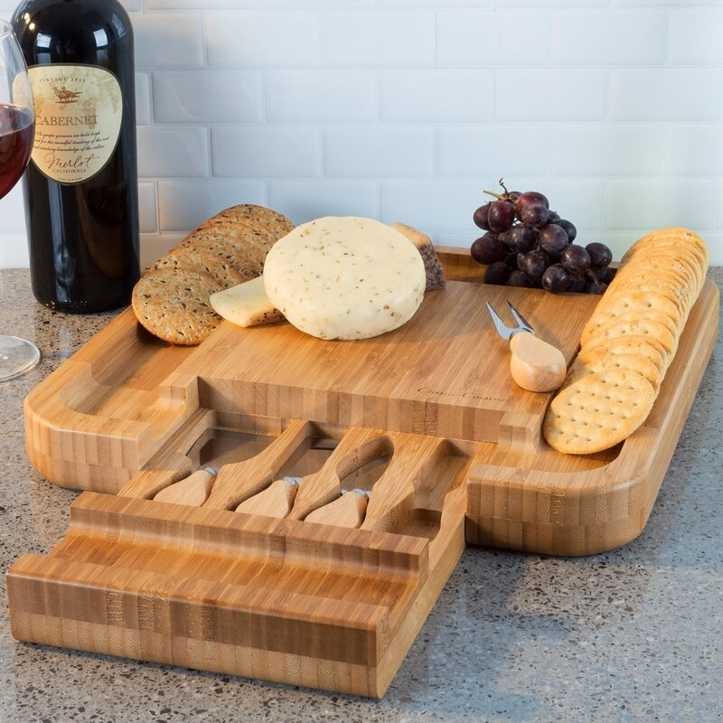 The cheeseboard with the drawer pulled out to show the set of knives and their storage area