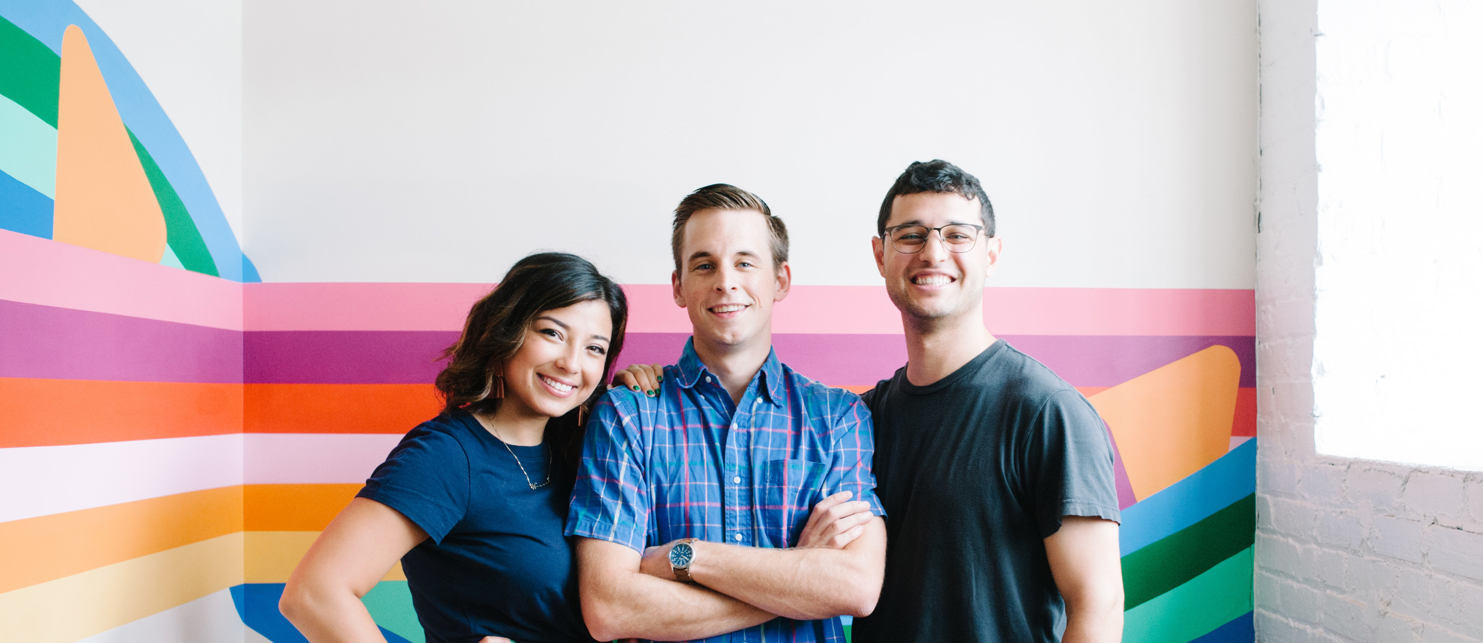 The three Nugget cofounders, Hannah Fussell, Ryan Cocca, and David Baron, standing against a colorful mural