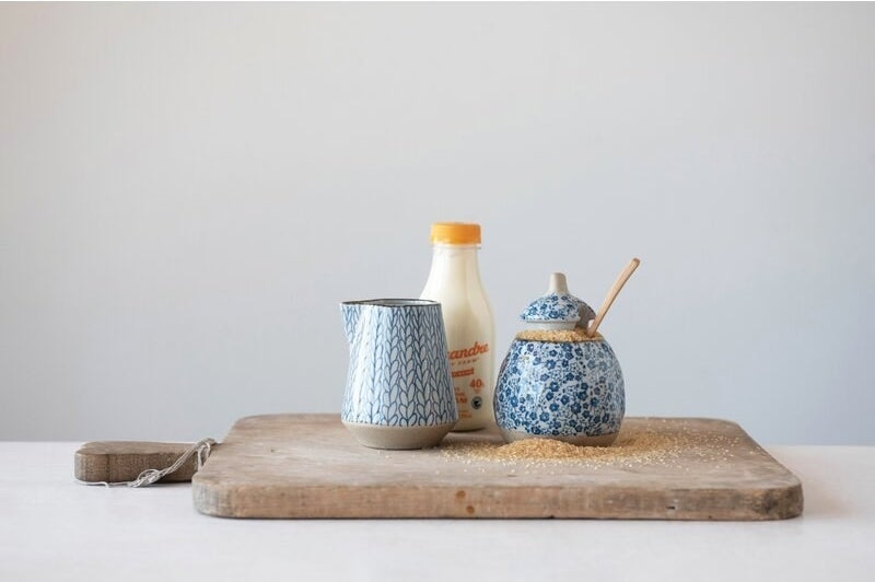 The sugar and creamer bowl beside each other on a cutting board to show their size and color