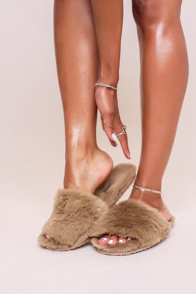 model wearing the faux fur slippers in tan