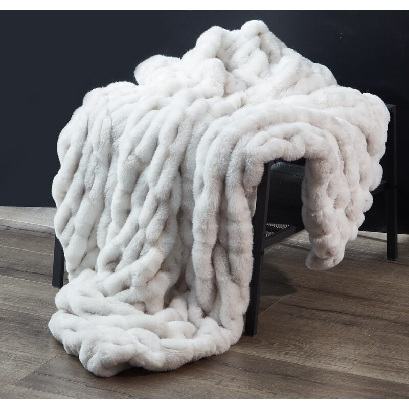The faux fur throw in light gray draped over a chair