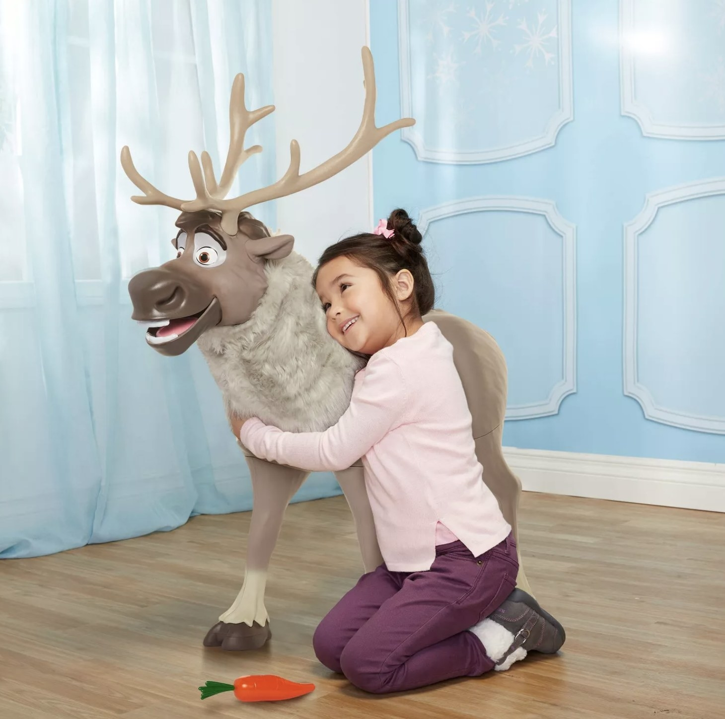 Child is holding a toy Sven from Frozen 2