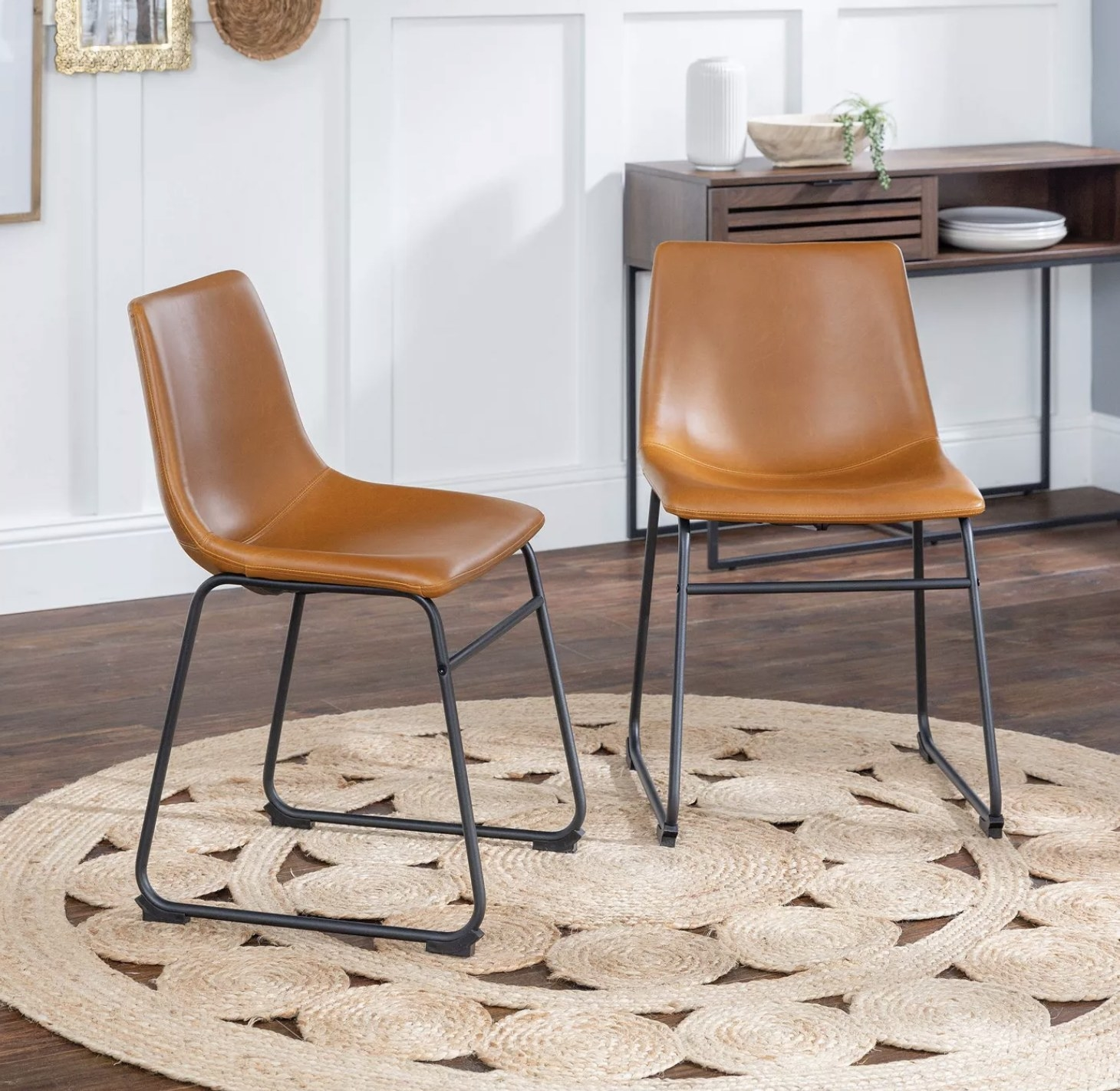 Two brown faux leather chairs in a living space