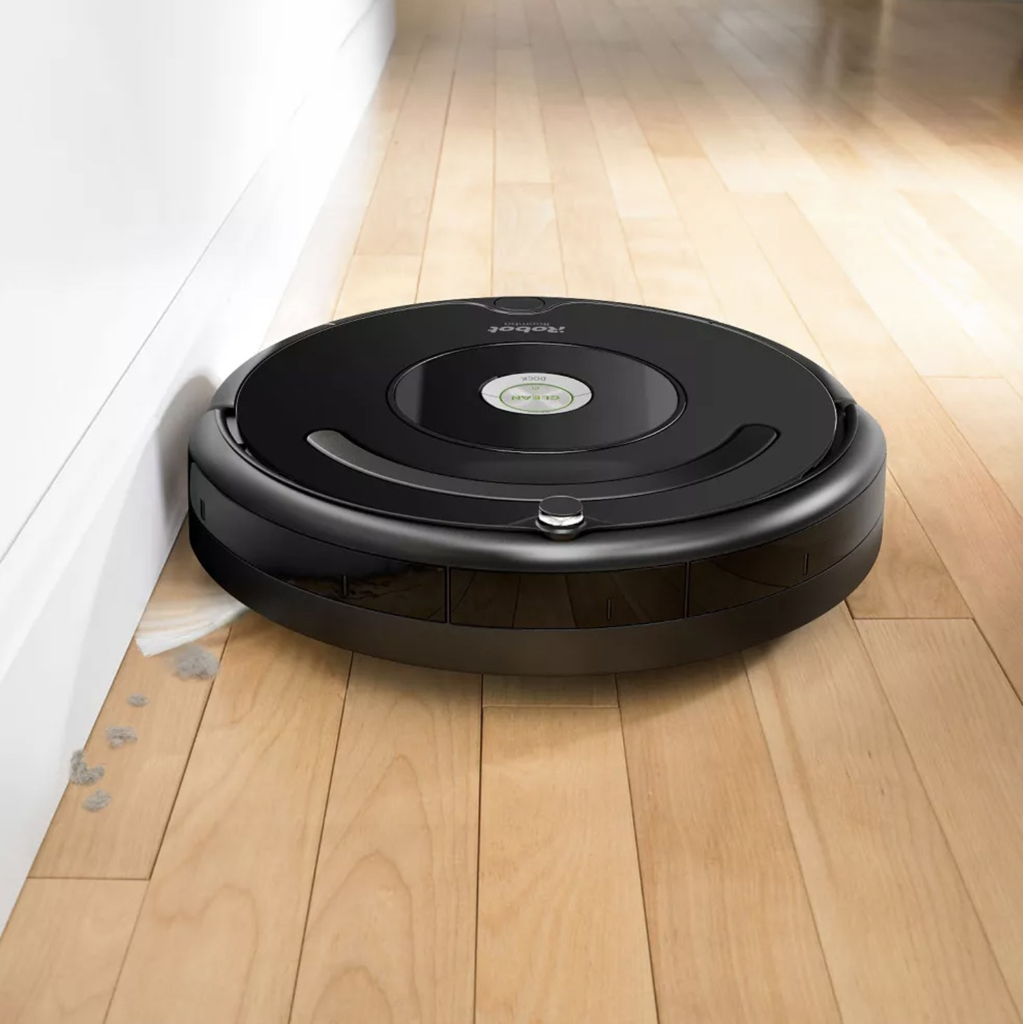 The robot vacuum cleaning dust from the edge of a wall