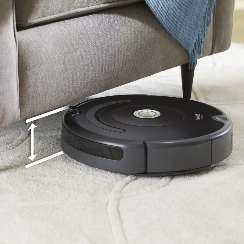 The Roomba cleaning under a couch to show its compact size