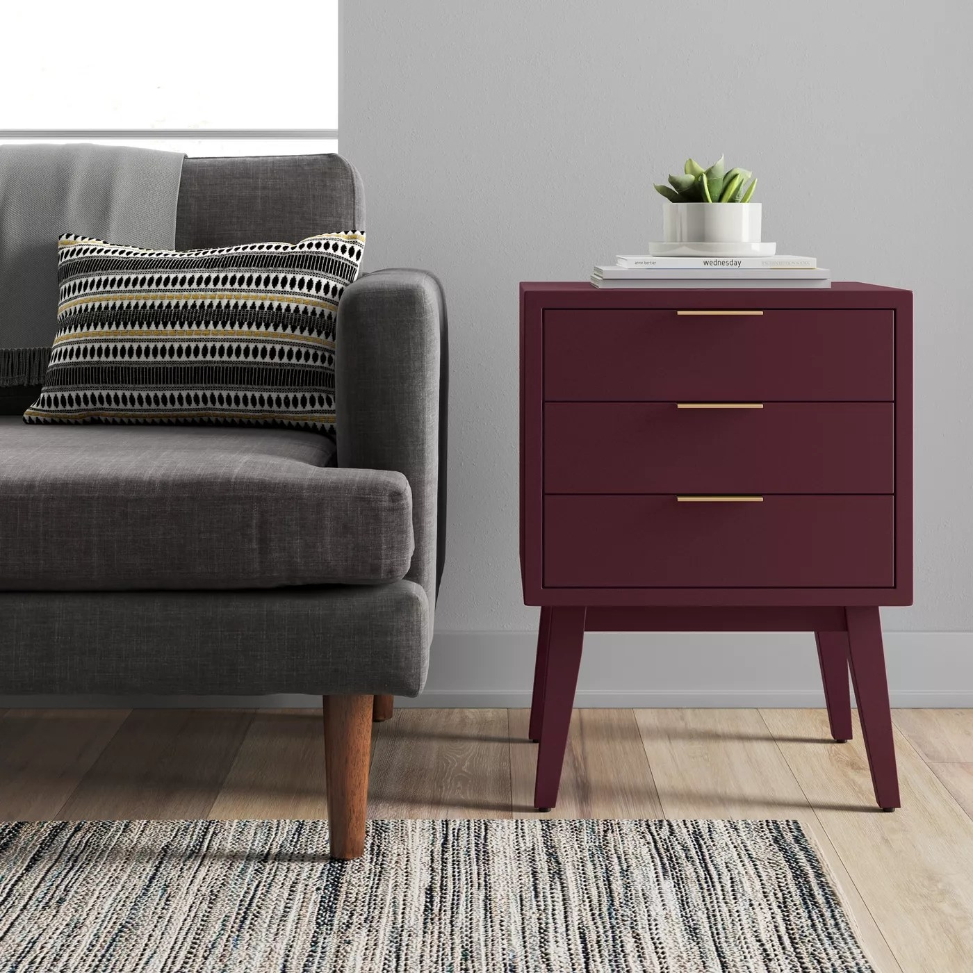 The maroon end table with three drawers and gold bar knobs