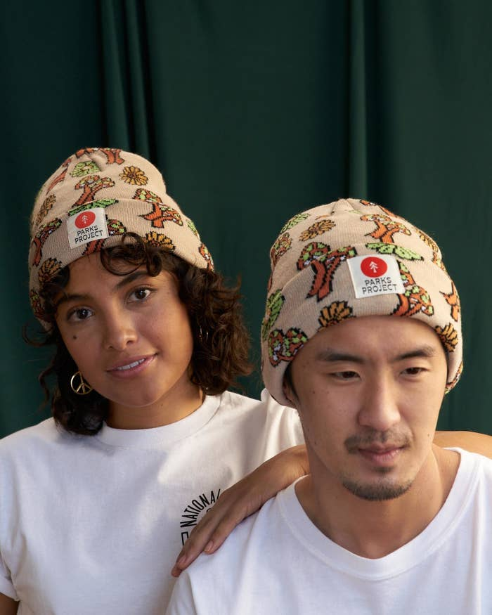 two models wearing the beanie with a Parks Project logo on the front