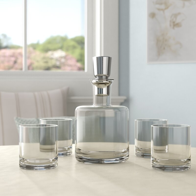 The transparent whiskey decanter set with four glasses on a table