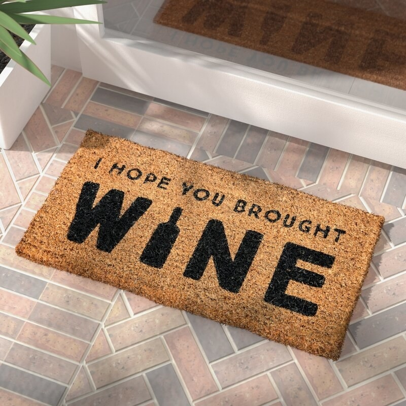 """The door mat, which reads """"I Hope You Brought Wine"""""""