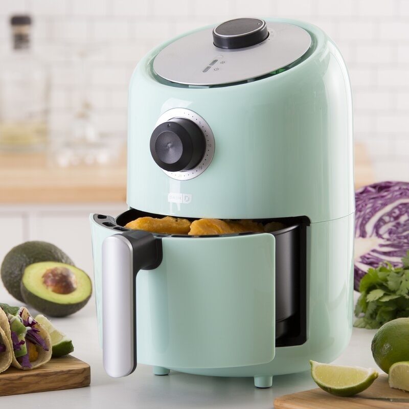 The blue air fryer with its draw open to show the drawer's space