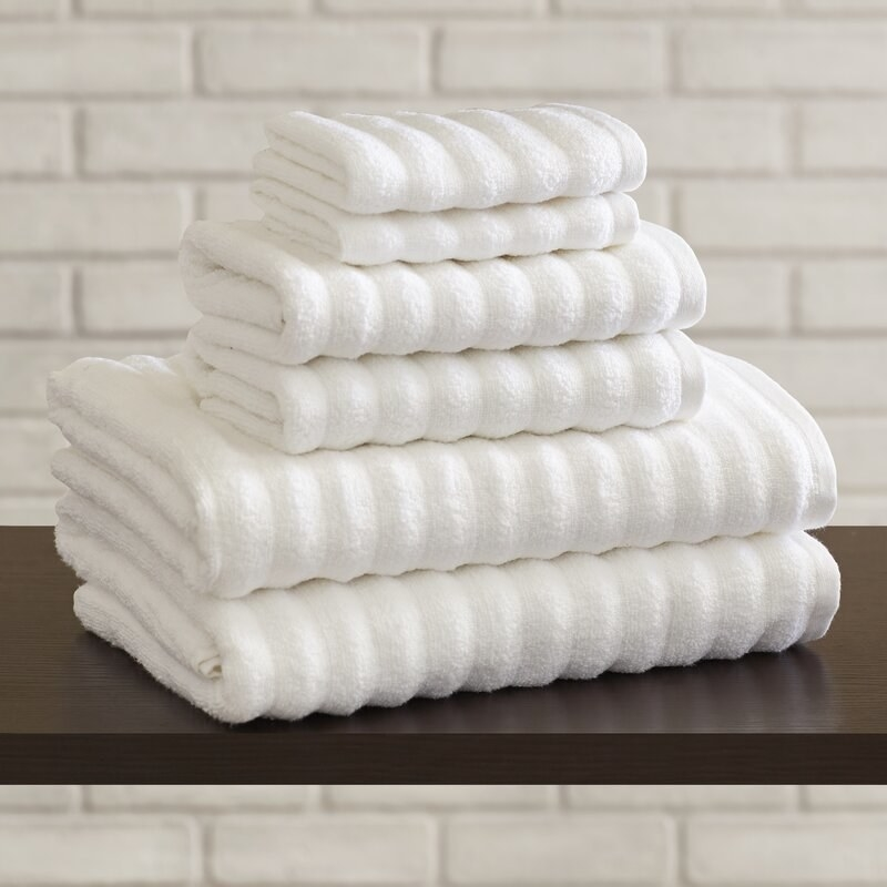 The white towels stacked to show their size and fluffiness