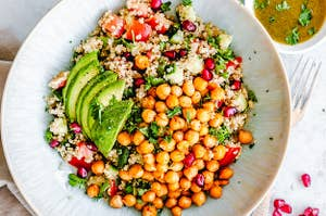 plate filled with cooked chickpeas, pomegranates, avocados, quinoa and tomatoes