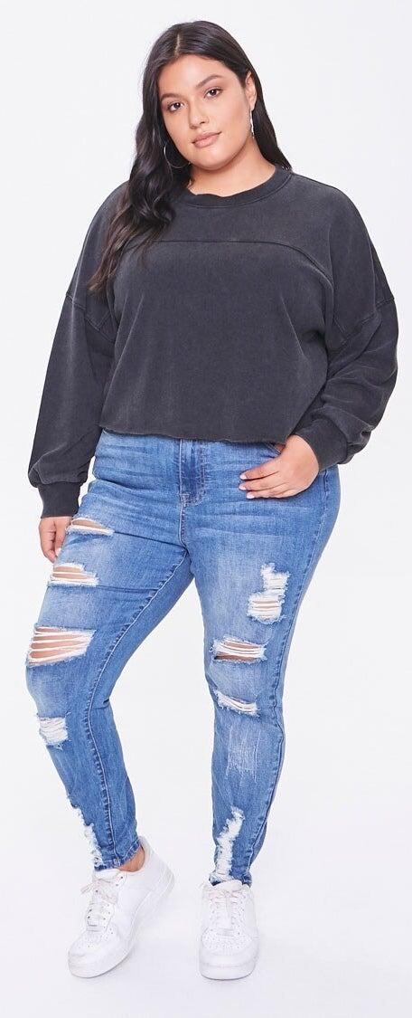 Model wearing distressed blue jeans