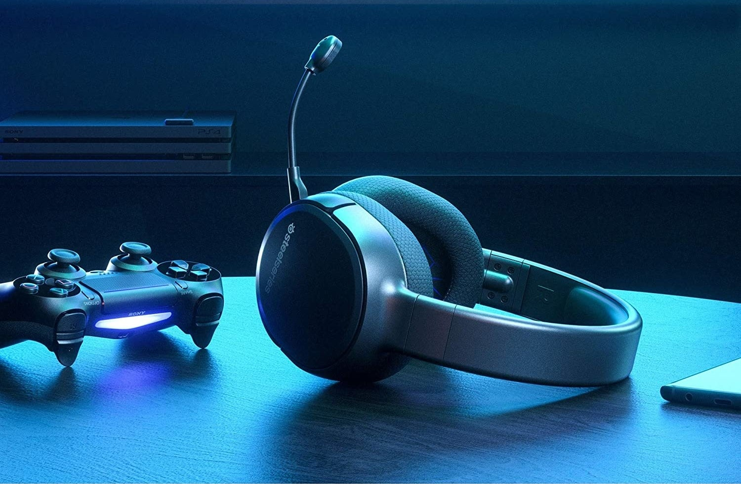 A wireless headset with microphone sits on a table near a game controller