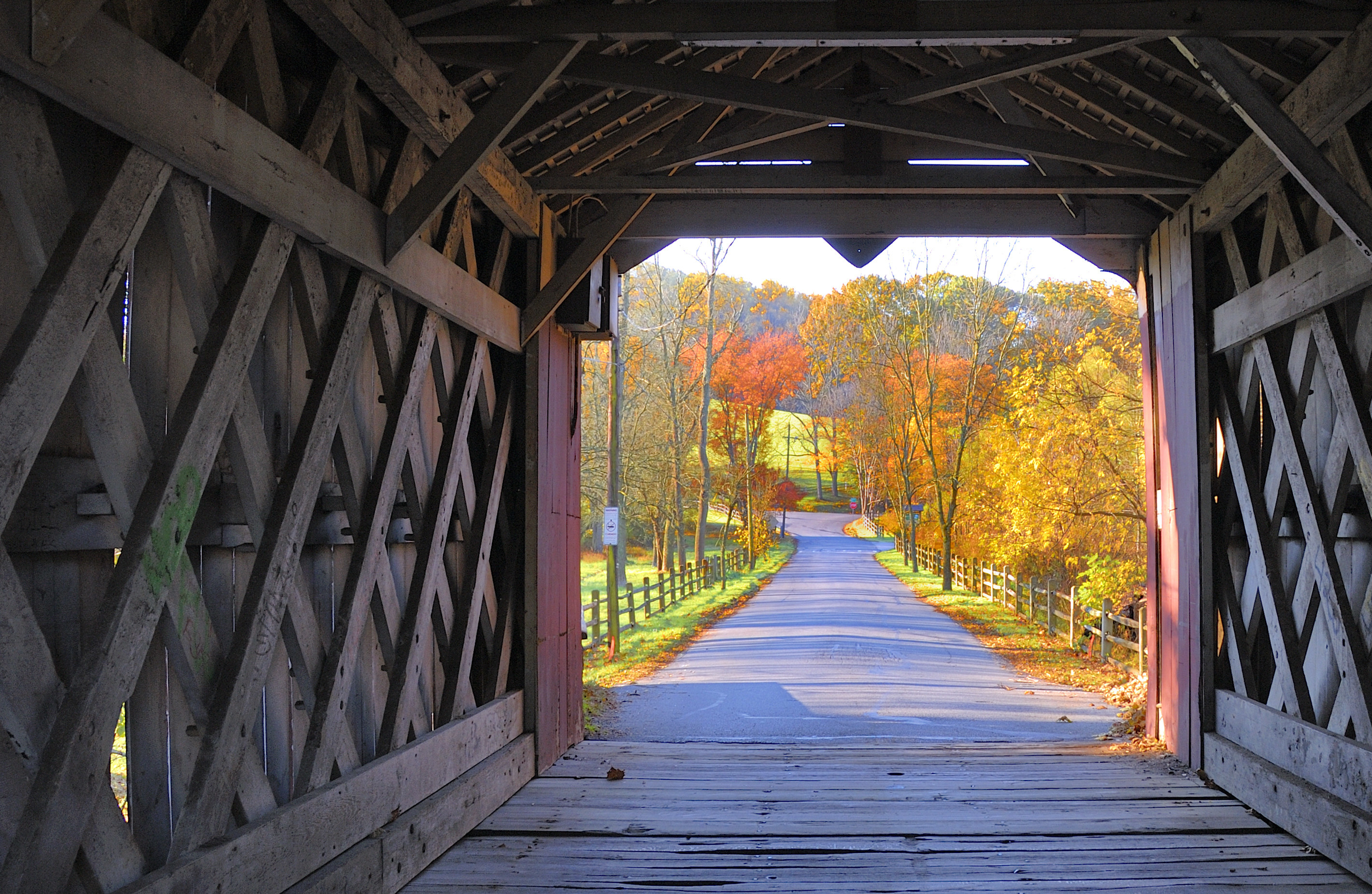 Inside the Ashland covered bridge with autumn trees showing on the other side