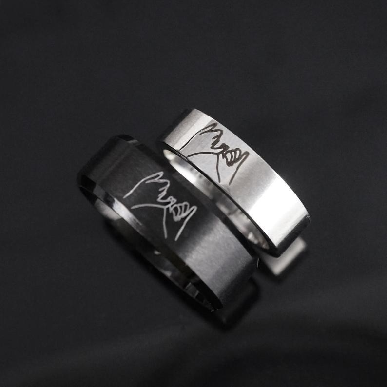 a black and metal ring with two hands pinky promising engraved on it