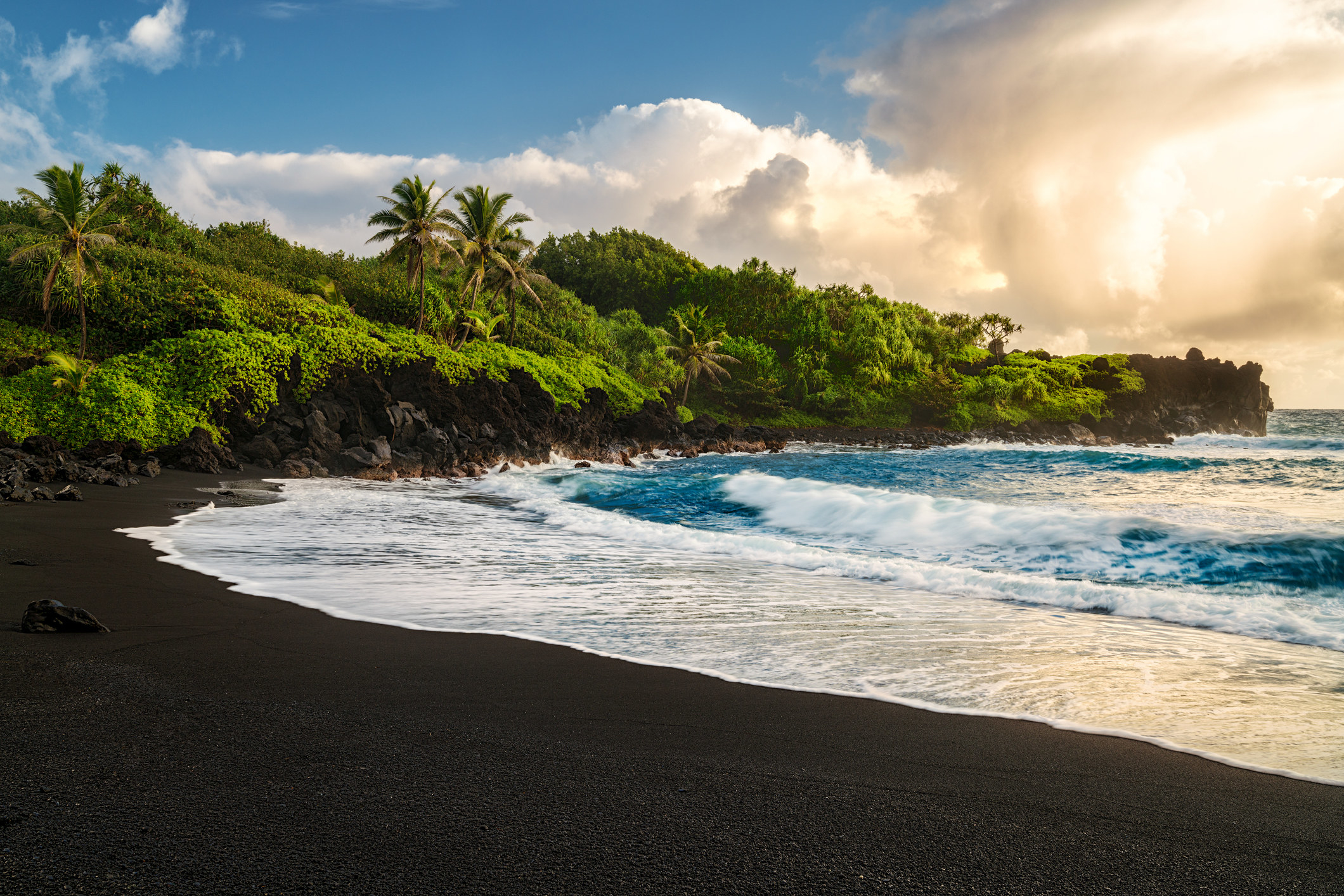 Waianapanapa Beach with black sand, blue waves, and lush greenery on the cliffside