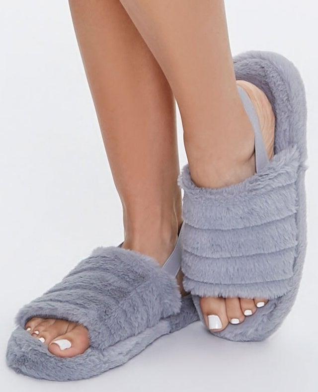 Model wearing grey slippers