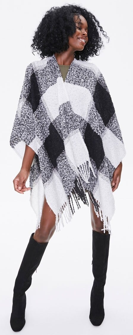 Model wearing black and white poncho
