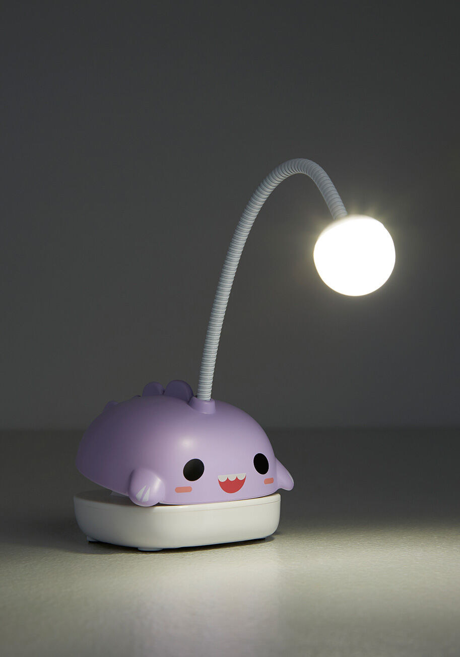 a lavender-colored book light shaped like an anglerfish