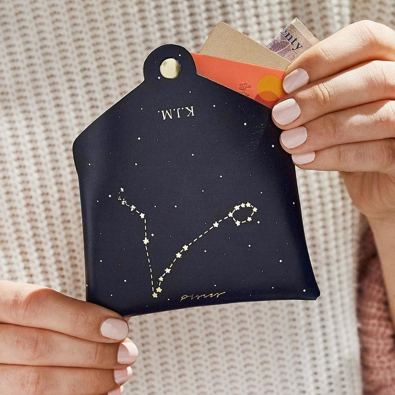 a model holding the coin purse with a constellation on it