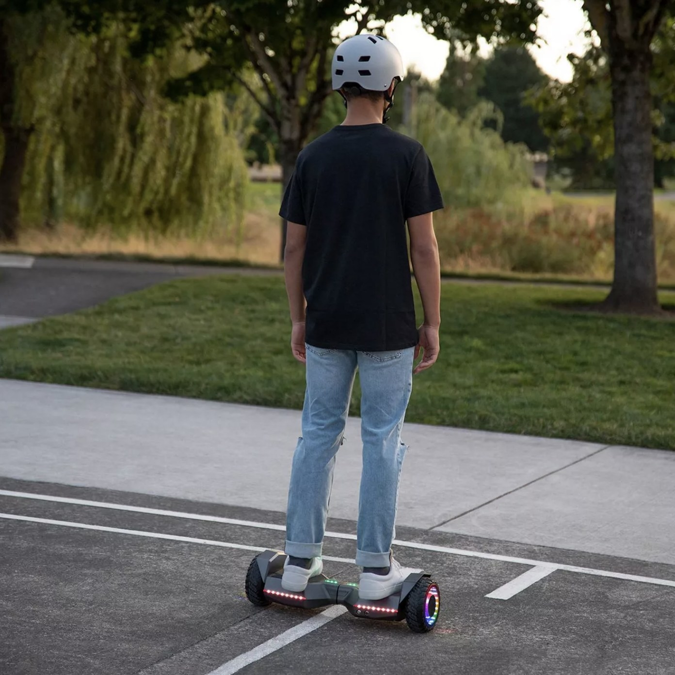 Model is standing on a hoverboard while wearing a helmet