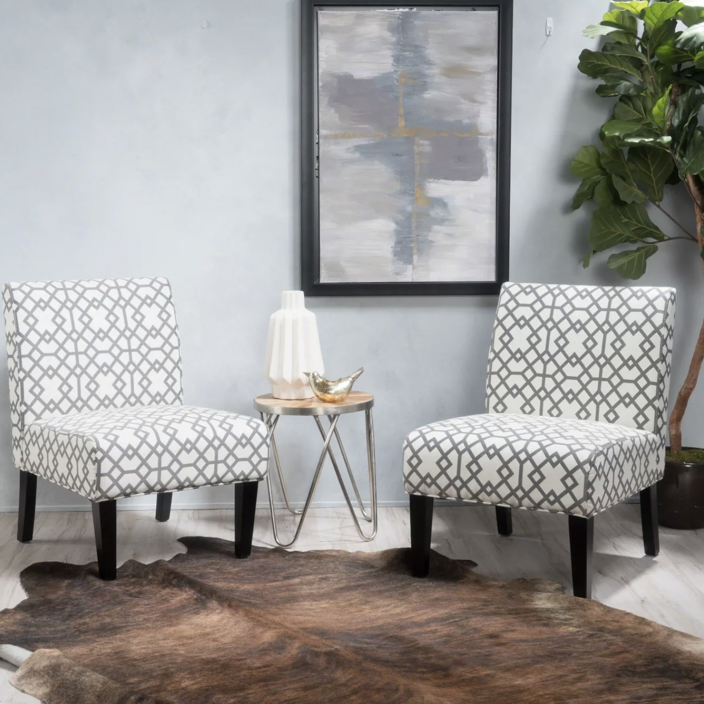 A set of two white accent chairs in a geometric pattern