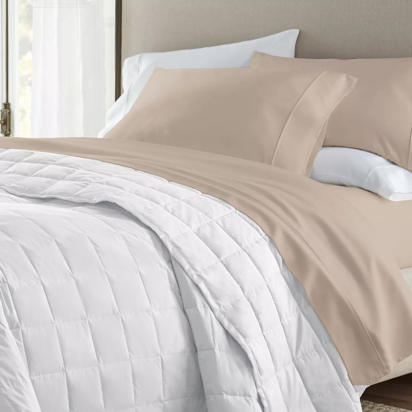 The taupe sheet set on a bed