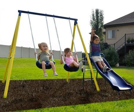 Outdoor yellow and blue playset with two swings and a slide