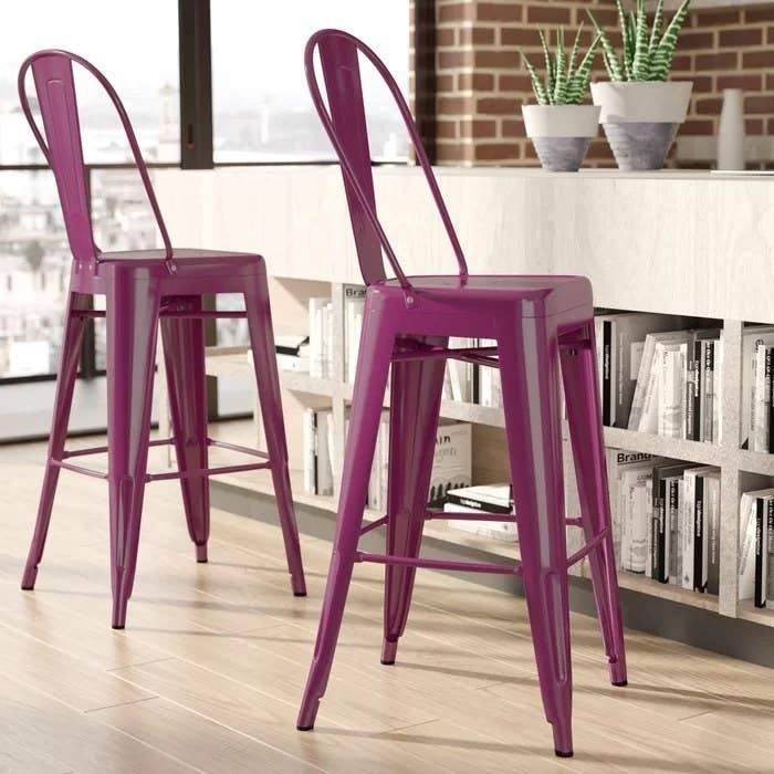 A close-up of two purple bar stools