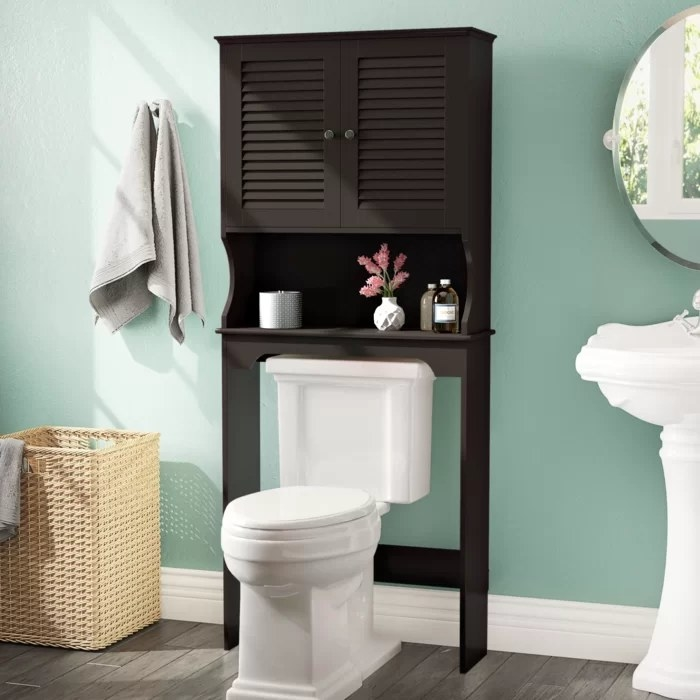 A black cabinet standing over the toilet