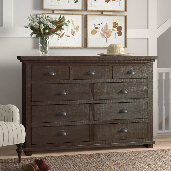 A dark grey dresser with flowers and a hat on top