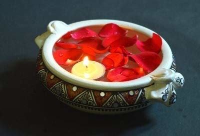 Rose petals and a tealight candle floating in the uruli.